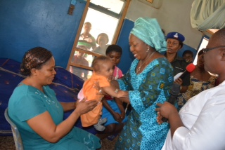 The wife of Abia state governor, Lady Mercy Odochi Orji carrying one of the babies whose mothers have been on detention at the Federal Medical Centre, Umuahia due to non payment of their discharged bills.