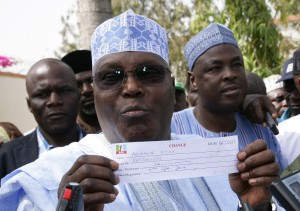 Former Vice President Atiku Abubakar displays his party card as member of APC in his ward in Jada, Adamawa State