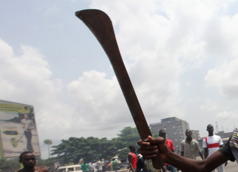 Anti-Gbagbo protester holds a machete near a roadblock and burning tyres in the Abobo area of Abidjan