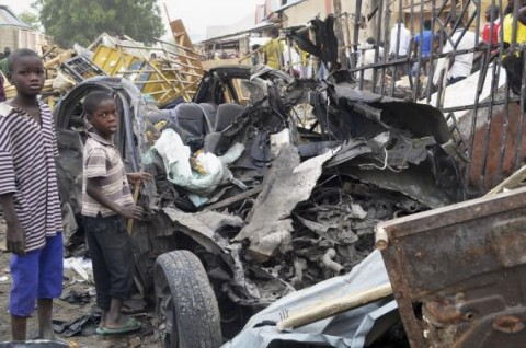 Two boys stand near the charred chassis of a vehicle after a bomb attack near a busy market area in Ajilari-Gomari near the city's airport, in Maiduguri March 2, 2014. At least 10 people were killed after a bomb went off at around 6 p.m. (1700 GMT) on Saturday in a busy market area in Ajilari-Gomari, witnesses and a police source said, in a region where the Islamist sect Boko Haram is pursuing a bloody insurgency. The final death toll was likely to be higher because dozens of people were trapped in the rubble, the witnesses said.