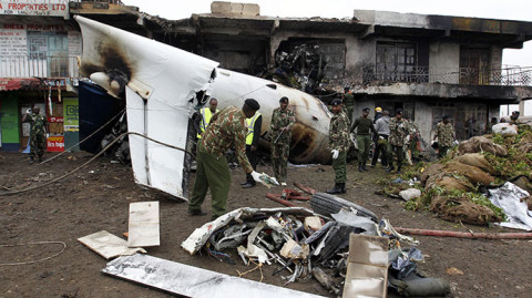 Security personnel attempt to retrieve bodies from wreckage of a cargo plane that crashed into a commercial building on outskirts of Nairobi