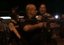 Overzelous officer points his semi-automatic gun at protesters threatening to kill them