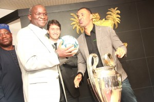 Lagos State Governor, Mr. Babatunde Fashola SAN (left), receiving the UEFA Champion League ball from the Heineken Ambassador and legendary Dutch International Footballer, Mr. Ruud Gullit (right) while the Marketing Director, Nigeria Breweries, Mr. Walter Direnth (middle) watches during the presentation of the UEFA Champions League Trophy to the Governor on a three Day tour of the State with the trophy as one of the selected three global cities organized by Heineken at the Lagos House Ikeja, on Thursday, March 13, 2014.